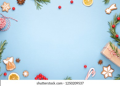 Blue Christmas background made of gigerbread cookies, rosemary branches, berries, gift box, Christmas wreath, cande cane lollipops and rope. Top view.