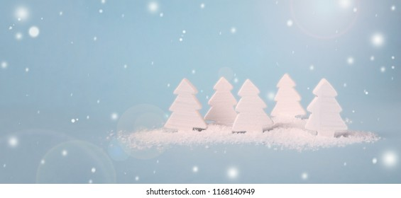 blue Christmas background with white wooden trees