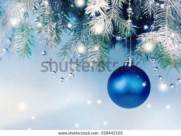 Blue Christmas ball hanging on Christmas tree.