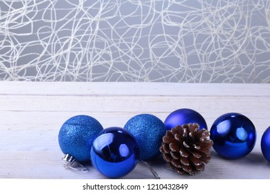 Blue Christmas balls, and fir cone on a wooden background