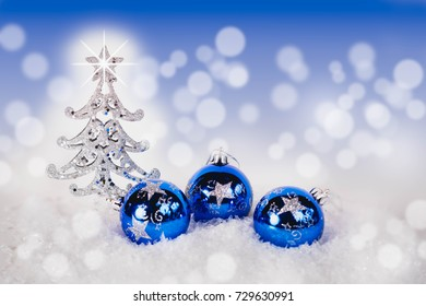 Blue Christmas balls and silver spruce with blue sparkling background. Festive winter and Finland 100  concept. Blue and silver xmas decoration with copy space.Copy space for text