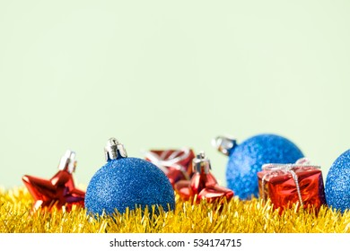 Blue christmas decoration ball and small red gifts on golden background. Merry christmas card