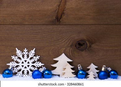 Blue Christmas Decoration On White Snow. Christmas Tree Balls, Snowflake And Christmas Tree.  Copy Space For Advertisement. Rustic, Vintage Brown Wooden Background.