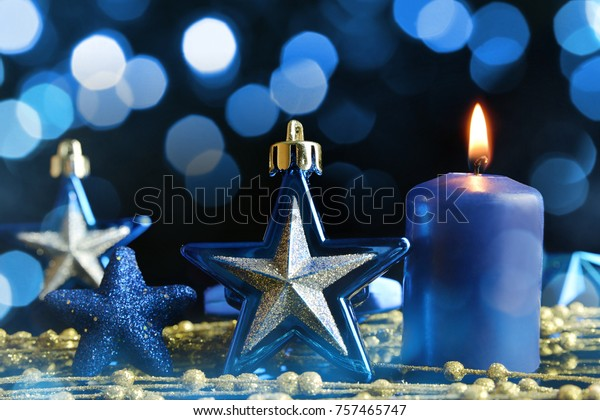 Blue Christmas decorations in the shape star and burning candle.