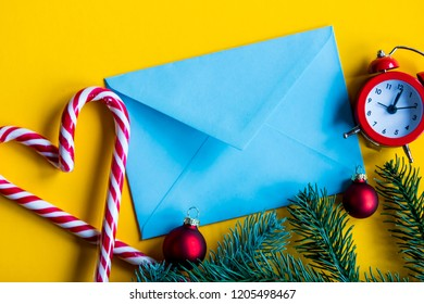 Blue christmas envelope and lolipop with alarm clock on yellow background