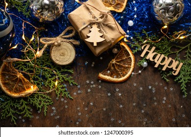 Blue christmas. gift in craft wrapping paper, ribbon, christmas balls. presents on dark wooden table