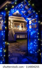 Blue Christmas Light Archway in front of house with snowman
