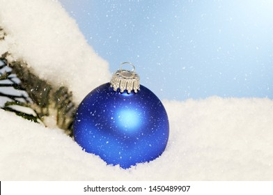 blue christmas ornament lying in snow
