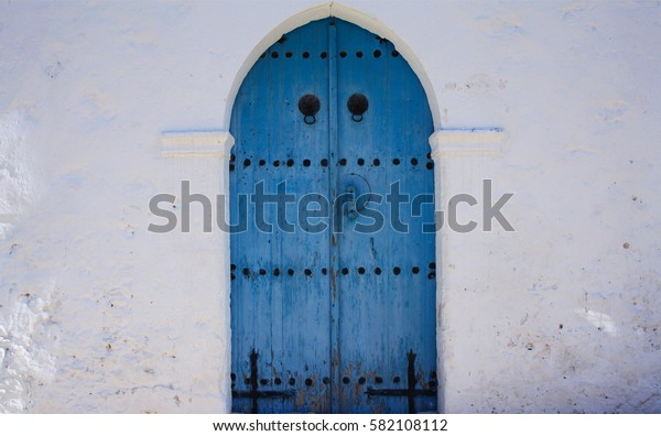 Blue church door with white stone wall, cyprus mediterranean style.