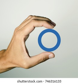 a blue circle, symbol of diabetes, in the hand of a young man, in support of diabetic people