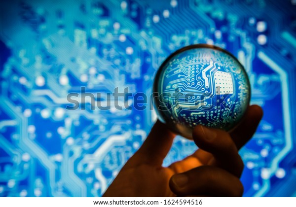 blue circuit board viewed through a handheld crystal ball