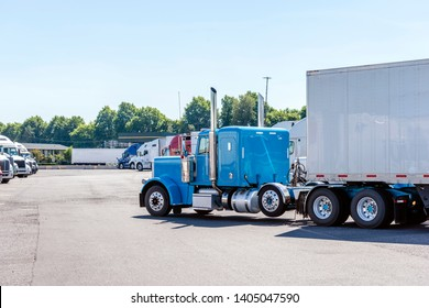 Blue classic American freight transportation big rig blue semi truck with tall chrome pipe transporting dry van semi trailer moving on the truck stop parking from row of another resting semi trucks