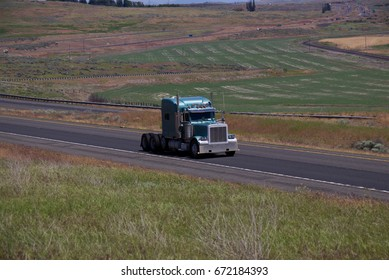 A Blue Classic Peterbilt Semi-Truck drives along a rural US highway with no trailer attached. June 20th, 2017 Oregon, USA