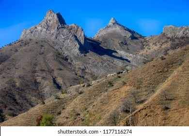 Blue clear sky, mountains and a herd of goats on a mountain slope