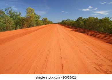 Blue clear sky over the red Australian rural road.