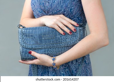 Blue closed clutch in womens hands. Fashion trendy crocodile leather hand bag. Beautiful and elegant blue women bag in hands. Fashion and style girl holding her powder-blue bag above and beneath