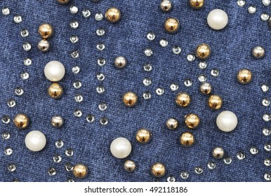 Blue cloth decorated with multicolor crystals. Background.