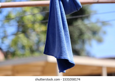 Blue cloth rag hanging drying on outdoor backyard metal clothesline on sunny day, laundry selective focus blurred background copy space