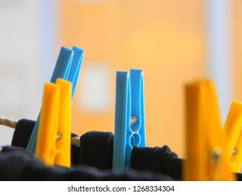 Blue clothespins fastening laundry on a clothesline, with the blurred image of yellow clothespins in the foreground (reverse bokeh), and a blurred background (bokeh)