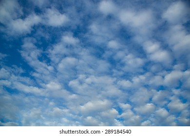 Blue and cloudy sky background with white clouds