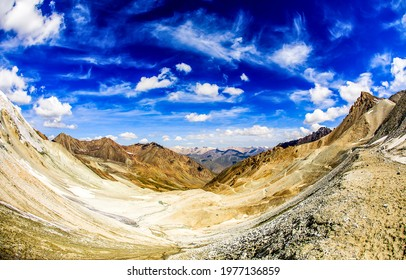 Blue cloudy sky over a mountain valley. Mountain valley panoramic landscape. Mountain valley panorama. Mountain sky - Shutterstock ID 1977136859