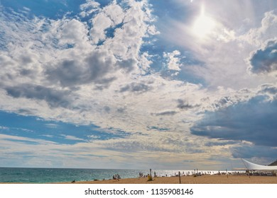A blue cloudy sky over the sea and sandy beach in Calella, Spain.
