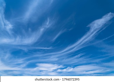 Blue cloudy sky with white cirrus clouds. Soft focus