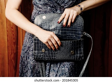 Blue clutch in hands. Trendy girl near wooden background. Stylish blue  dress and open clutch. Stylish outfit and fashion concept.