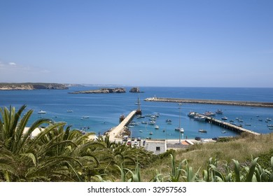 The blue coasts of southern Portugal, the Algarve. Sagres old port with traditional fishing boats, and a full sized replica of a Portuguese 16th century sailing ship