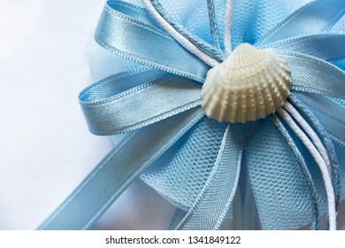 blue cockade with shell on a white background, symbol for the birth of a child