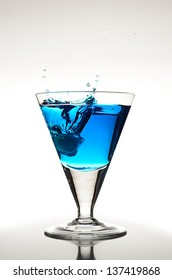 Blue cocktail with an ice cube and a big splash