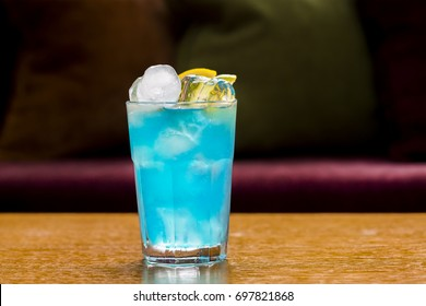 Blue cocktail with ice and lemon