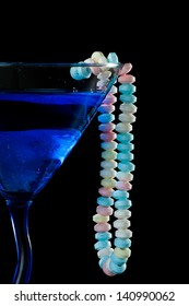 blue cocktail isolated on a black background with a candy necklace wrapped around it
