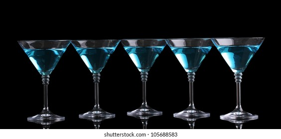 Blue cocktail in martini glasses isolated on black