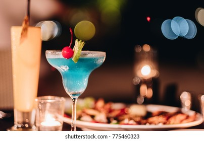 Blue cocktail on the glass with the bbq food in the night dinner party
