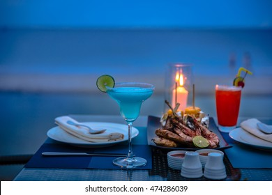 Blue cocktail on the tropical sea sunset background