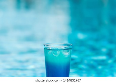 Blue coctail with ice in the glass on the swimming pool background. Resort tropical hotel in summer day and fresh water. Blurred backgraund with copy space.