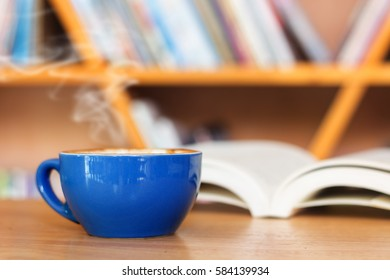 Blue coffee cup with book on table. Selective focus.