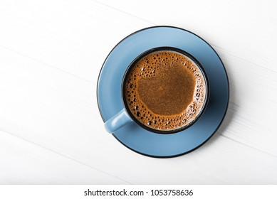 Blue coffee cup on a white wood table. top view