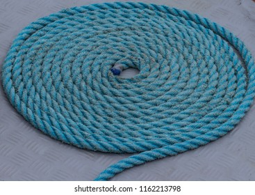 Blue coiled mooring rope on boat