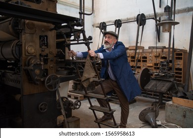 Blue collar worker climbing on a old printing machine
