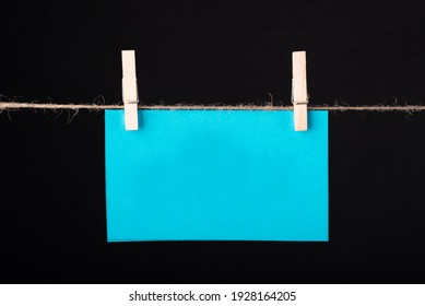 Blue color blank empty sticky note hanging with a wire on black background