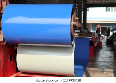 Blue color coated coiled steel in metal sheet rolling machine ; for tile manufacturing ; metal sheet coated steel that made from hot-dip ; industrial equipment background