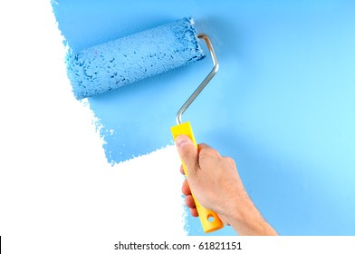 blue color painting wall with roller in hand
