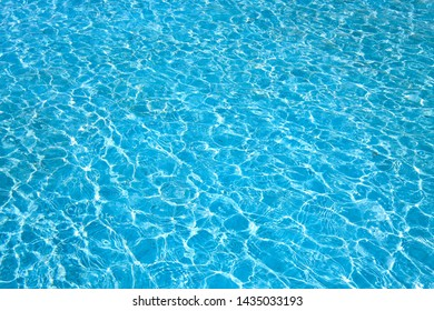 Blue color water in swimming pool rippled water with sun reflections background.