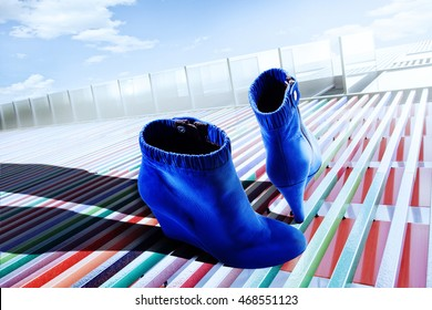 Blue Colored Ankle Boots Standing On A Platform In Sunlight
