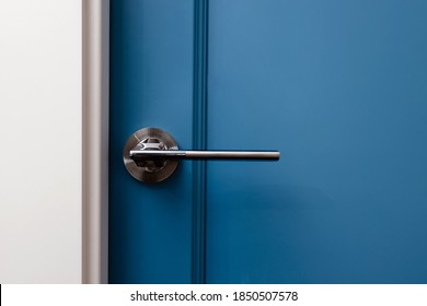 Blue colored door with handle in modern design apartment close-up