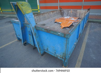 Blue colored dump bin at open space parking area.