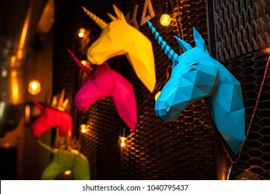 Blue and colorful  paper unicorn on dark background. Origami toy. Origami pegasus. Head of unicorn of paper.
