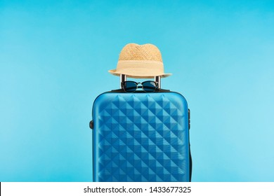 blue colorful travel bag with handle, sunglasses and straw hat isolated on blue